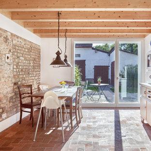 Ejemplo de comedor de cocina rural, grande, sin chimenea, con paredes blancas, suelo de baldosas de terracota y suelo rojo