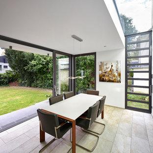Ispirazione per una sala da pranzo minimal chiusa e di medie dimensioni con pareti bianche, pavimento in ardesia, nessun camino e pavimento beige