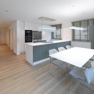 Idee per una sala da pranzo aperta verso la cucina minimal di medie dimensioni con pareti bianche, pavimento in vinile, camino classico, cornice del camino in intonaco e pavimento beige