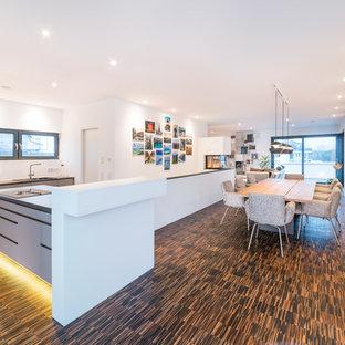 Foto de comedor de cocina actual, grande, con paredes blancas, suelo de bambú, chimenea de doble cara, marco de chimenea de yeso y suelo marrón