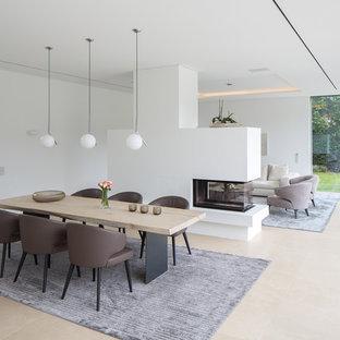 Modelo de comedor contemporáneo, de tamaño medio, abierto, con paredes blancas y chimenea de doble cara