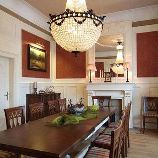 Imagen de comedor clásico, grande, con paredes rojas, suelo de madera clara, estufa de leña y marco de chimenea de madera