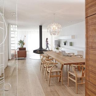 Cette image montre une très grand salle à manger ouverte sur le salon design avec un sol en bois clair, un manteau de cheminée en métal et un mur blanc.