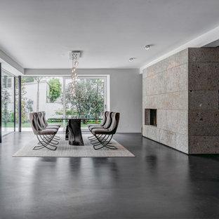 Imagen de comedor contemporáneo, extra grande, abierto, con paredes blancas, chimenea tradicional y marco de chimenea de hormigón