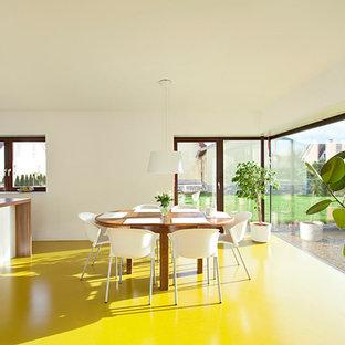Réalisation d'une salle à manger ouverte sur la cuisine design de taille moyenne avec un mur blanc et un sol jaune.