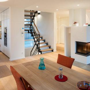 Cette image montre une salle à manger ouverte sur le salon design de taille moyenne avec un mur blanc, un sol en bois clair, une cheminée double-face et un manteau de cheminée en plâtre.