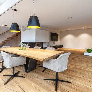 Offenes, Großes Modernes Esszimmer mit grauer Wandfarbe, hellem Holzboden, Eckkamin, verputzter Kaminumrandung und beigem Boden in Sonstige