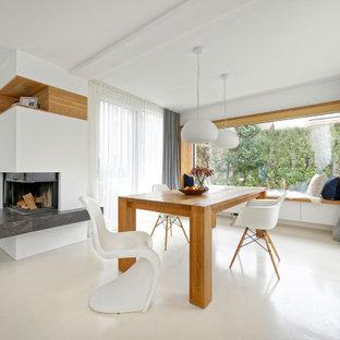 Immagine di una grande sala da pranzo aperta verso il soggiorno design con pareti bianche, pavimento in compensato, camino ad angolo e pavimento beige