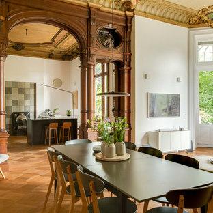 Offenes, Geräumiges Modernes Esszimmer mit weißer Wandfarbe, braunem Holzboden und braunem Boden in Düsseldorf