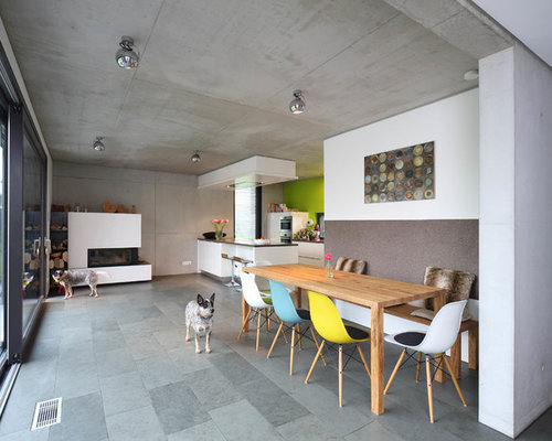 Offenes, Großes Modernes Esszimmer Mit Kaminofen, Verputztem Kaminsims,  Grauem Boden Und Weißer Wandfarbe