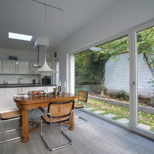 Mittelgroße Moderne Wohnküche mit weißer Wandfarbe und grauem Boden in Dortmund