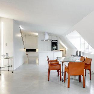 Diseño de comedor de cocina minimalista, grande, con paredes blancas y suelo de cemento