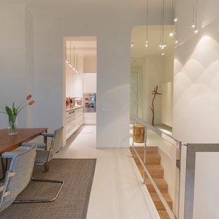 Foto di una sala da pranzo aperta verso il soggiorno design di medie dimensioni con pareti bianche, nessun camino e pavimento bianco