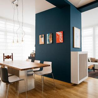 Offenes, Großes Modernes Esszimmer ohne Kamin mit blauer Wandfarbe, braunem Holzboden und braunem Boden in Berlin