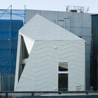 Imagen de fachada de casa beige, industrial, pequeña, a niveles, con revestimiento de metal, tejado a la holandesa y tejado de metal