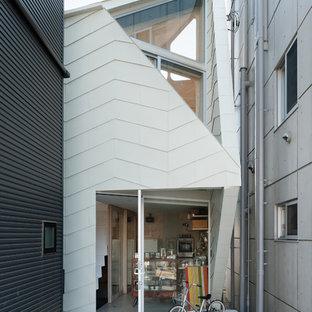 Diseño de fachada de casa beige, industrial, pequeña, a niveles, con revestimiento de metal, tejado a la holandesa y tejado de metal