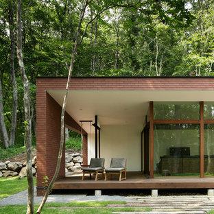 Foto på ett mellanstort funkis brunt hus i flera nivåer, med tegel, sadeltak och tak i metall