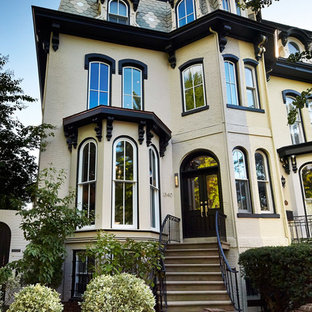 Example of an ornate beige three-story exterior home design in DC Metro