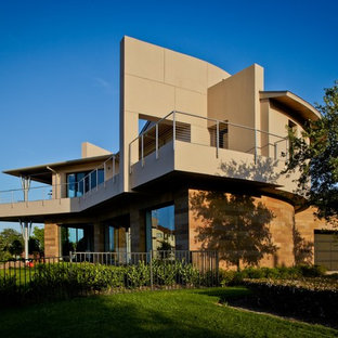 Example of a huge minimalist beige three-story mixed siding house exterior design in Houston with a hip roof and a metal roof