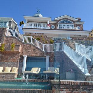 Diseño de fachada roja, costera, grande, de tres plantas, con revestimiento de ladrillo y tejado a dos aguas