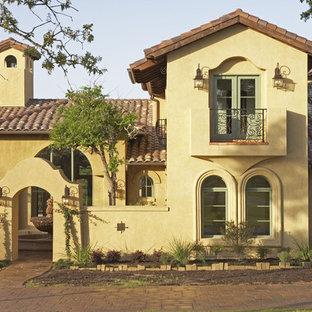 Design ideas for a mediterranean two floor house exterior in Austin.