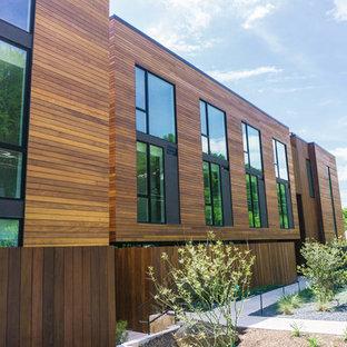 Пример оригинального дизайна: большой, трехэтажный, деревянный многоквартирный дом в современном стиле