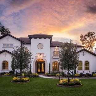 Large tuscan beige two-story stucco house exterior photo in Houston with a hip roof and a shingle roof