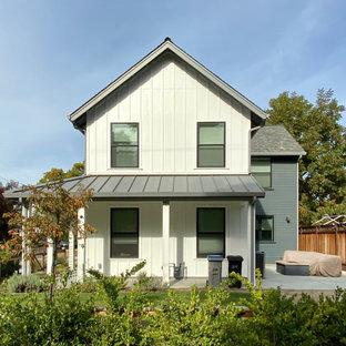 Réalisation d'une grand façade de maison multicolore tradition à un étage avec un toit à quatre pans et un toit en shingle.