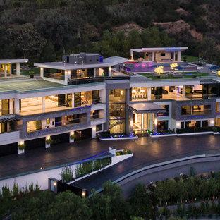 На фото: огромный, четырехэтажный, серый частный загородный дом в стиле модернизм с облицовкой из камня, плоской крышей и крышей из смешанных материалов