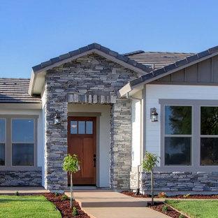 Modelo de fachada de casa gris, pequeña, de una planta, con revestimientos combinados, tejado a dos aguas y tejado de teja de barro