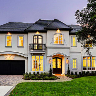 Photo of an arts and crafts two-storey stucco beige house exterior in Houston.