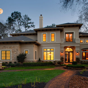 Large mediterranean two-storey stucco beige exterior in Houston with a hip roof.