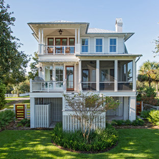 Imagen de fachada de casa blanca, marinera, de tamaño medio, con revestimiento de madera, tejado a dos aguas y tejado de metal