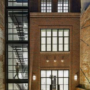 Esempio della facciata di una casa a schiera contemporanea a tre piani con rivestimento in mattoni