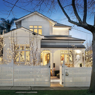 Traditional two-storey white exterior in Melbourne with wood siding.