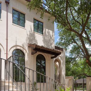 Inspiration for a large mediterranean beige two-story stucco house exterior remodel in Houston with a hip roof and a tile roof