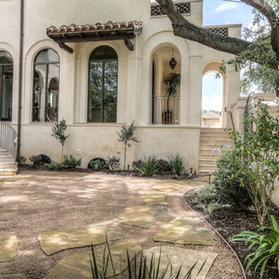Example of a large tuscan beige two-story stucco house exterior design in Houston with a hip roof and a tile roof