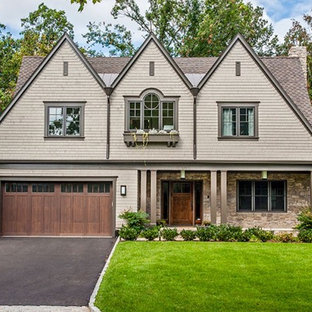 Large cottage chic beige two-story brick exterior home photo in New York with a clipped gable roof
