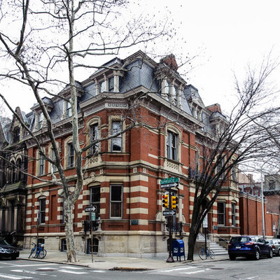 Huge traditional red three-story brick flat roof idea in Philadelphia
