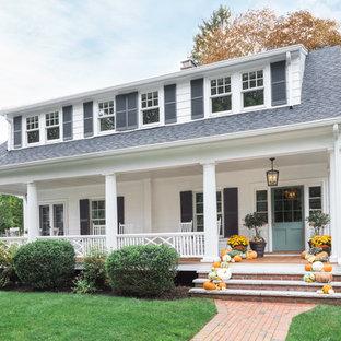Esempio della villa bianca classica a due piani con copertura a scandole