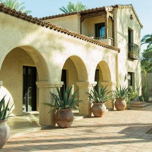 Foto de fachada de casa beige, de estilo americano, extra grande, de dos plantas, con tejado a dos aguas, tejado de teja de barro y revestimiento de adobe