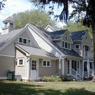 Example of a large classic gray two-story wood gable roof design in New York