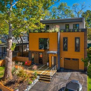 Imagen de fachada naranja, actual, grande, de dos plantas, con revestimiento de vinilo y tejado plano