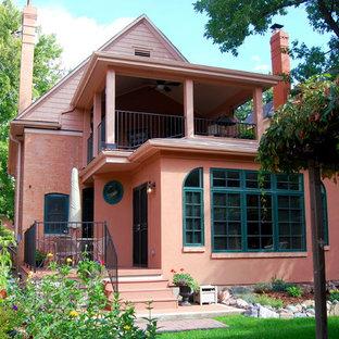 Esempio della facciata di una casa rosa classica con rivestimento in mattoni