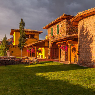 Mid-sized mediterranean yellow two-story stone gable roof idea in Other
