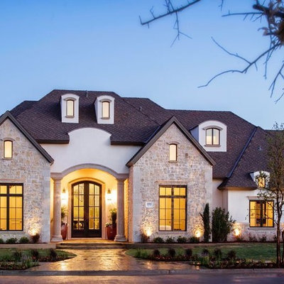 Example of a large classic white two-story stucco exterior home design in Austin with a shingle roof
