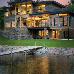 Idées déco pour une très grand façade en pierre grise contemporaine à deux étages et plus avec un toit à quatre pans.