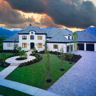 Foto de fachada de casa blanca, mediterránea, extra grande, de tres plantas, con revestimiento de ladrillo, tejado a cuatro aguas y tejado de teja de madera