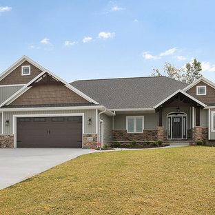 Idée de décoration pour une grand façade de maison verte craftsman de plain-pied avec un revêtement en vinyle, un toit à deux pans et un toit en shingle.
