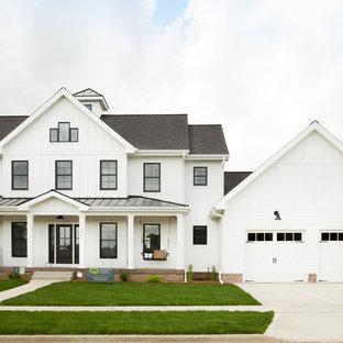 Immagine della facciata di una casa unifamiliare bianca country a due piani con rivestimento in vinile